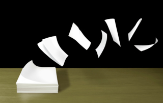 Papers flying from stack on desk